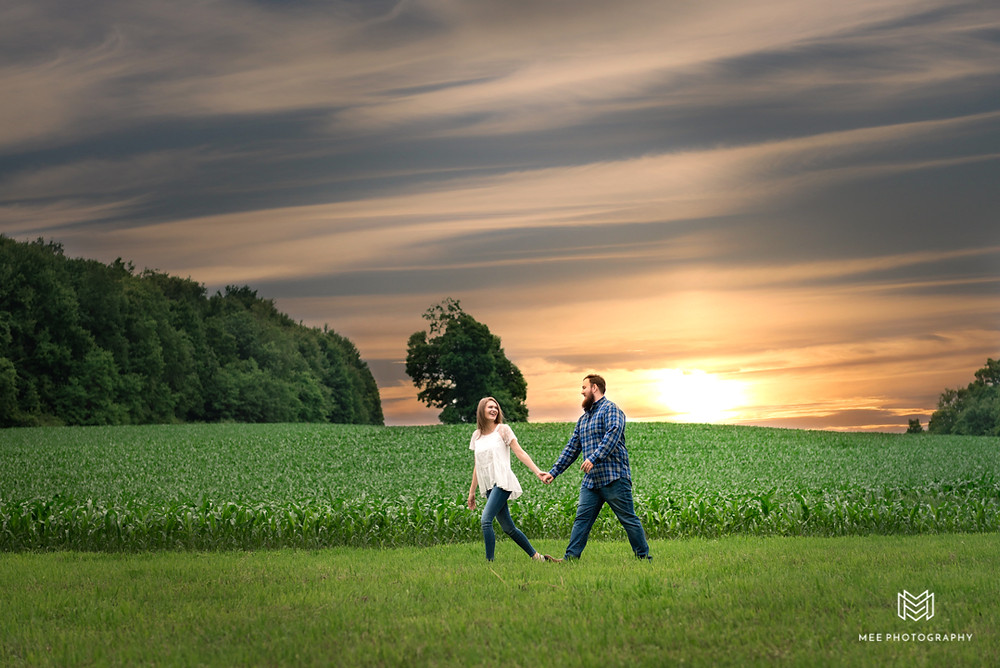 Country engagement photos in a field at sunset at Chanteclaire Farm. Couple posed walking and holding hands.