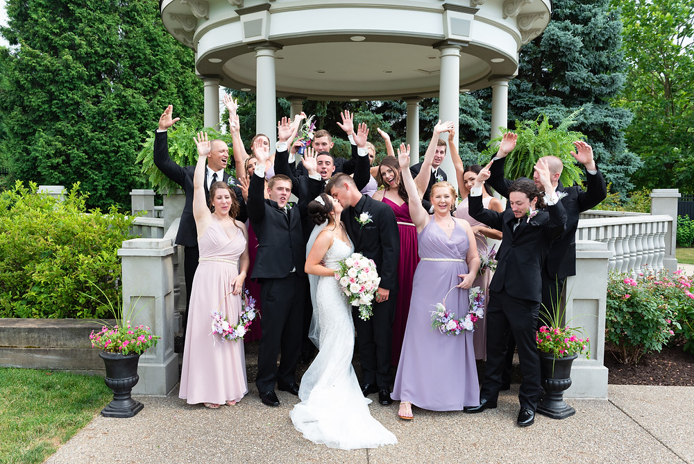 Bridal party cheering while bride and groom kiss