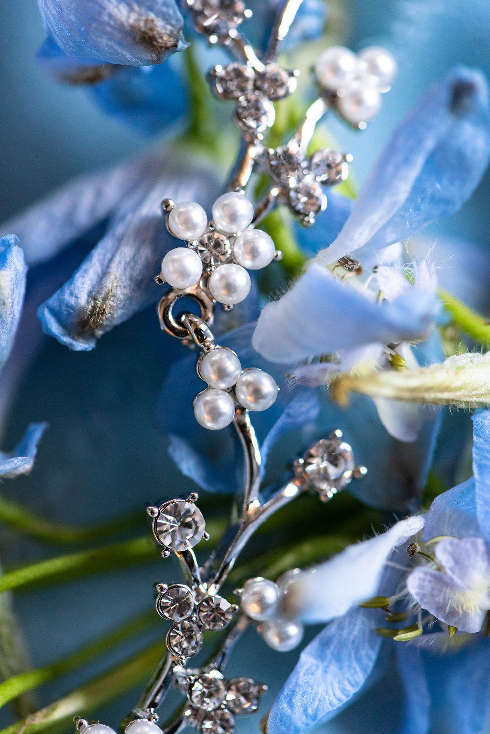 Bridal pearl necklace laid on blue flowers