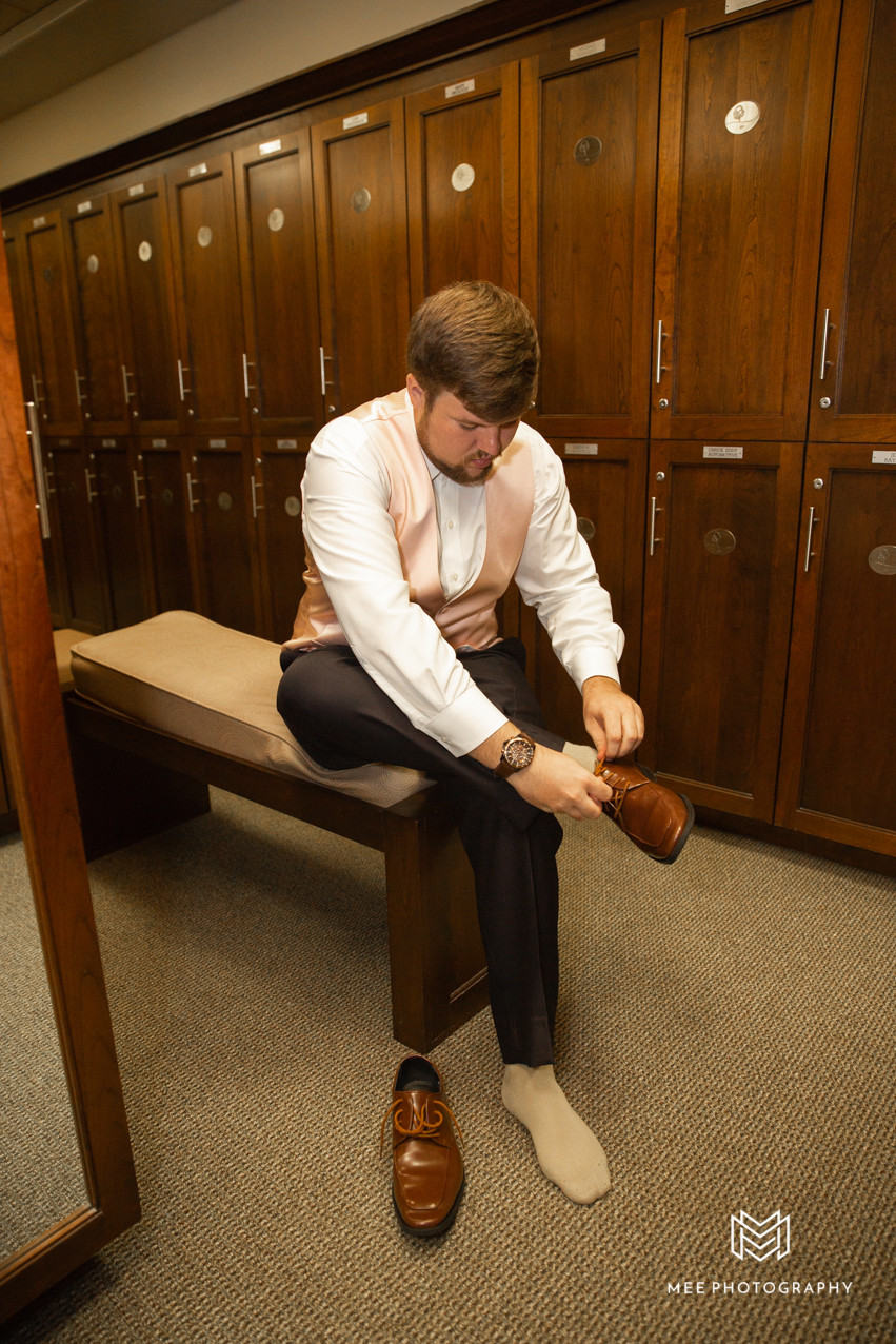 Groom putting on brown shoes and blush vest