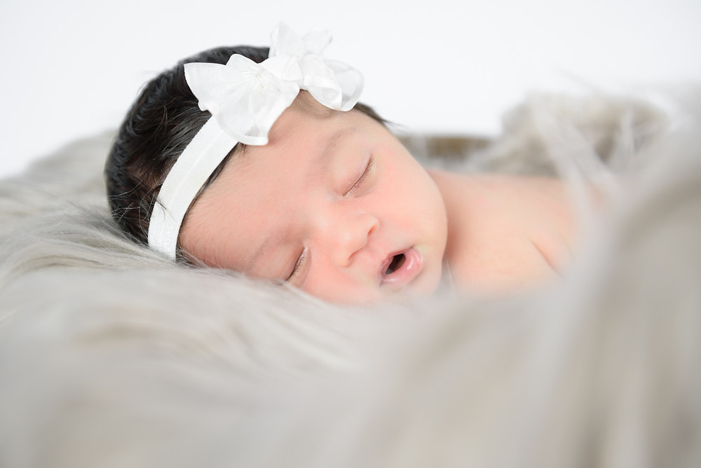 Newborn baby girl sleeping with her mouth open on a fur blanket during her first photo shoot.