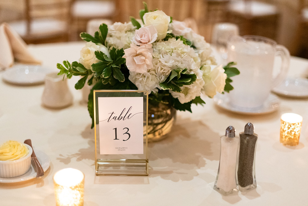 Ivory bouquet centerpiece with gold table number at the Circuit Center