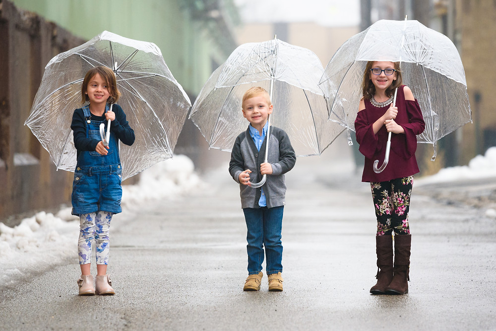 Three siblings laughing in the rain under clear umbrellas during their photo shoot in Weirton, Wv.