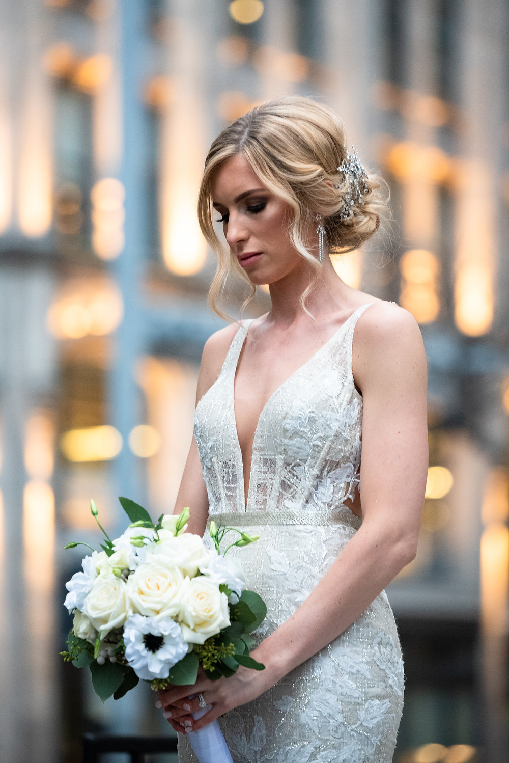 Bride wearing Berta dress, holding and ivory rose bouquet