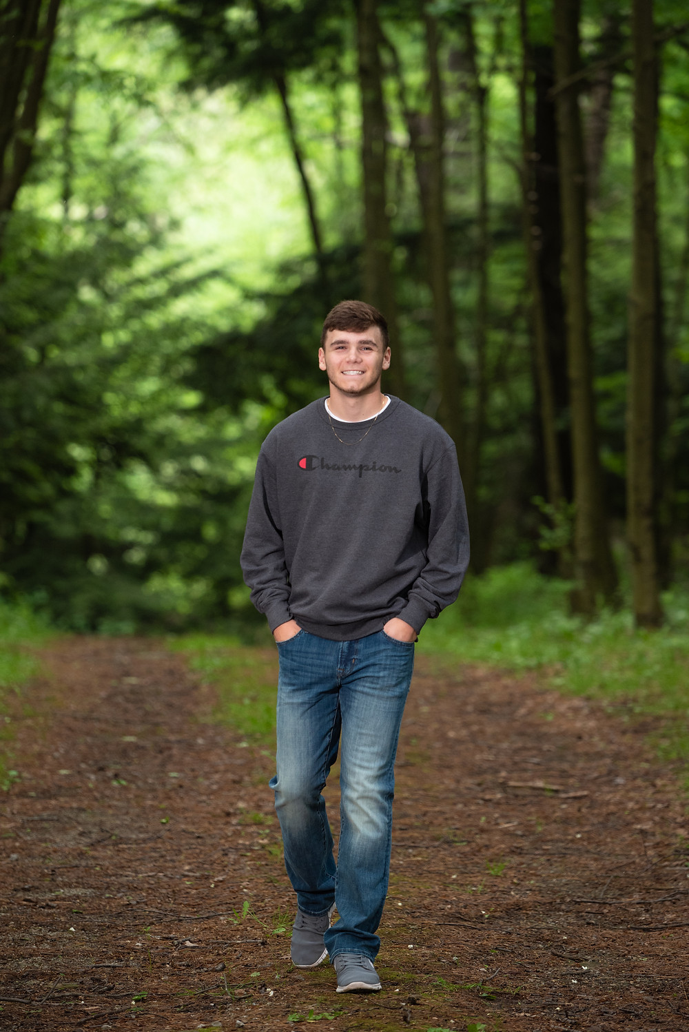 Senior guy walking down a path in the woods during his senior photoshoot near Pittsburgh