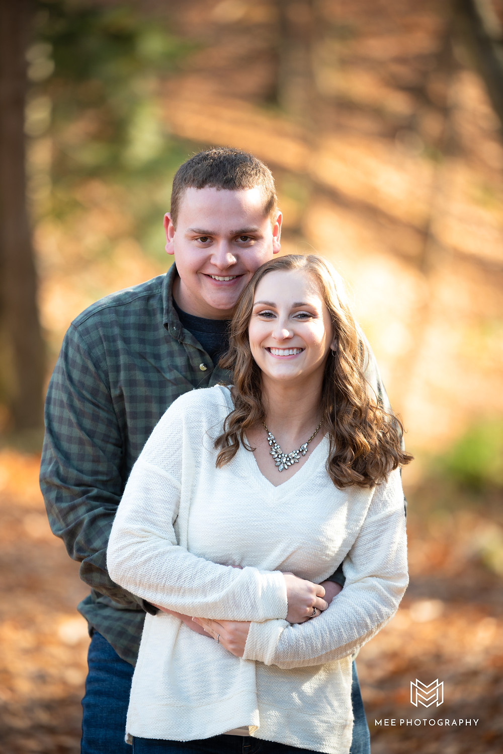 Girl wearing a white sweater and guy wearing a plaid shirt during their fall engagement session in the woods