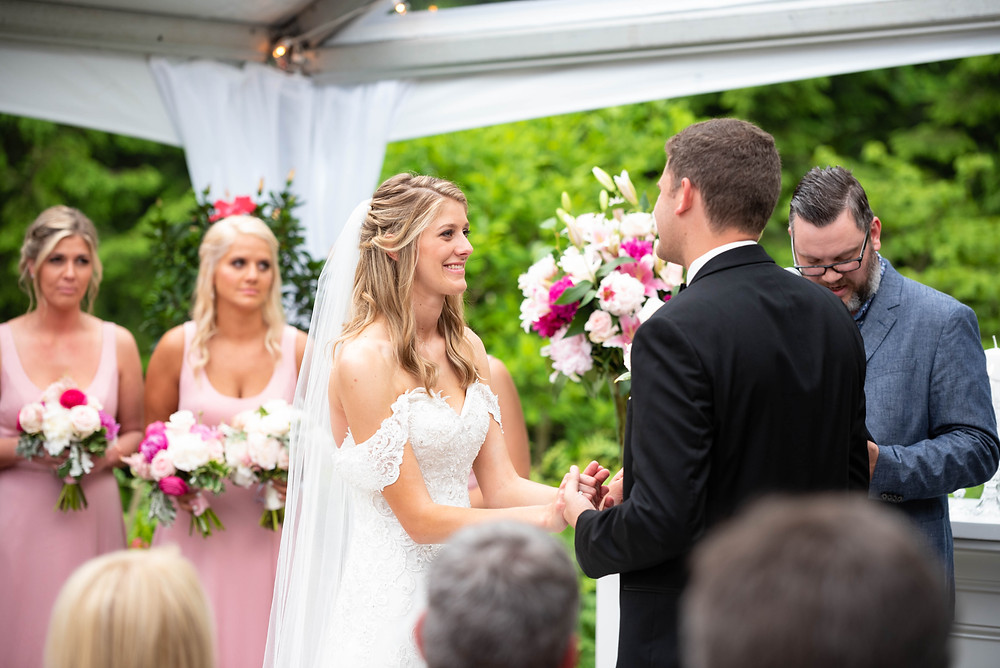 Bride and groom reciting vows during tented wedding ceremony in Pennsylvania