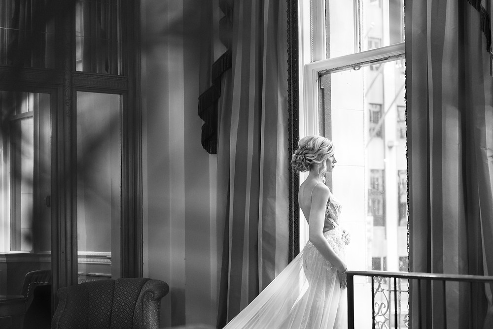 Bride looking out the window at th Omni William Penn Hotel in Pittsburgh