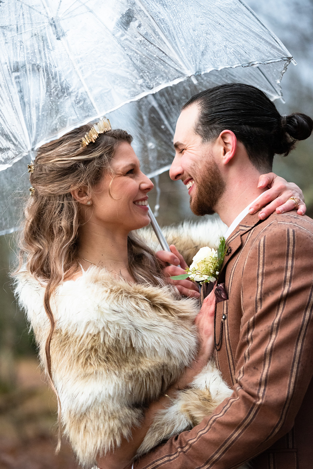 Bride and groom portrait with clear umbrella in the rain