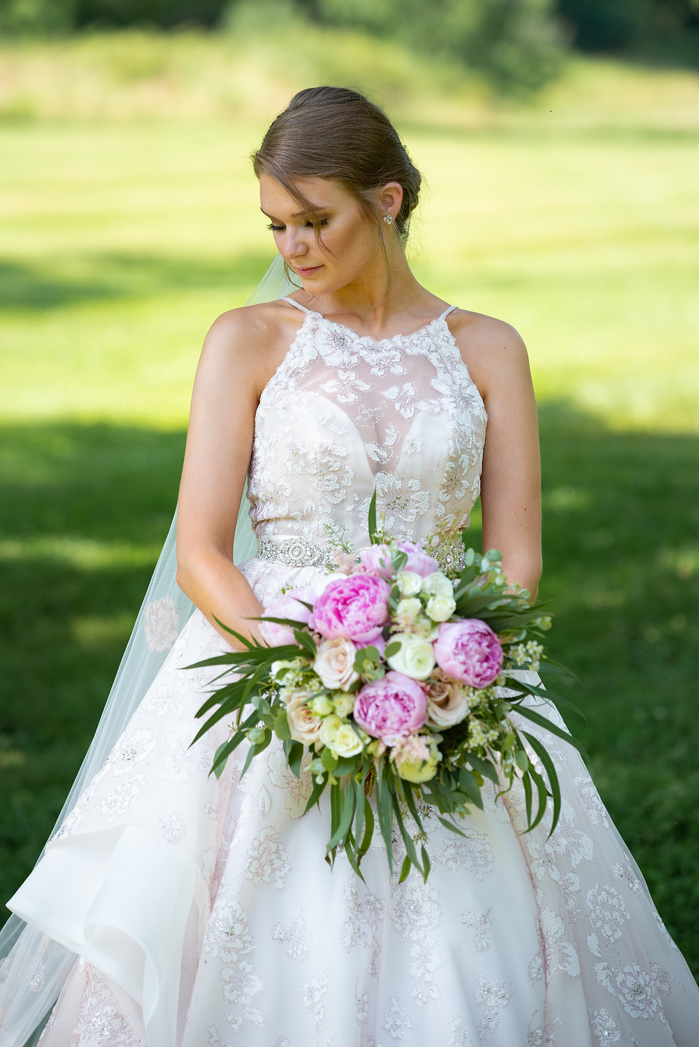 Bridal portrait with bride wearing a pink dress and holding pink peonies