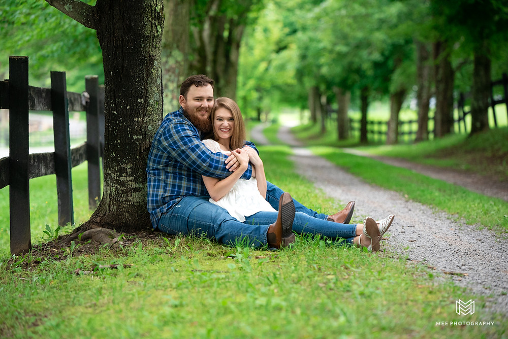 Engagement photos at Chanteclaire Farm in Maryland with couple posed sitting along gravel road.