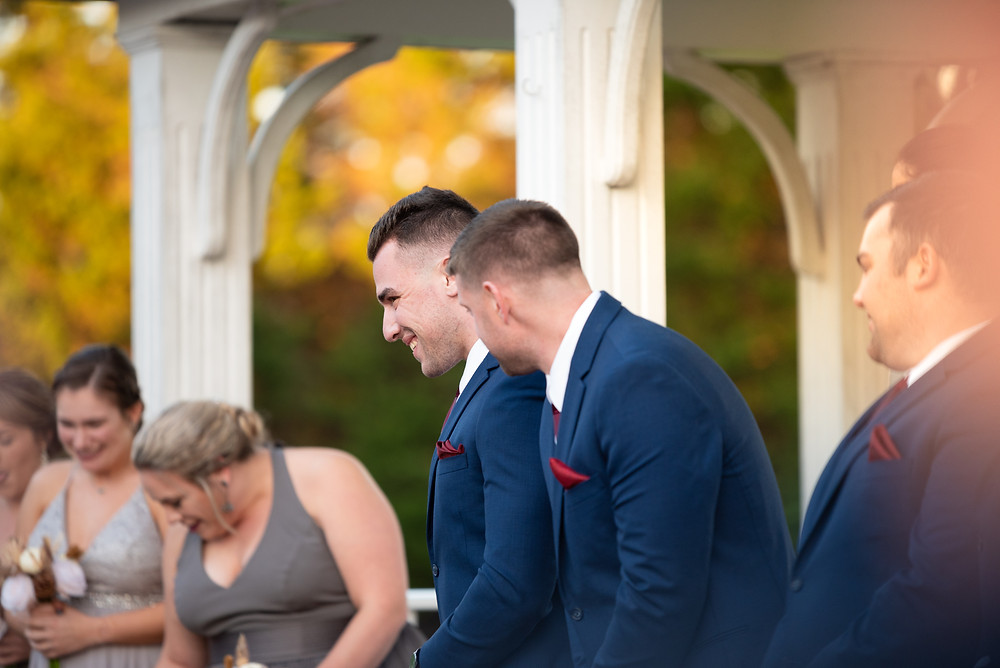 Groom laughing at the flower girl walking down the aisle during their fall ceremony at sunset