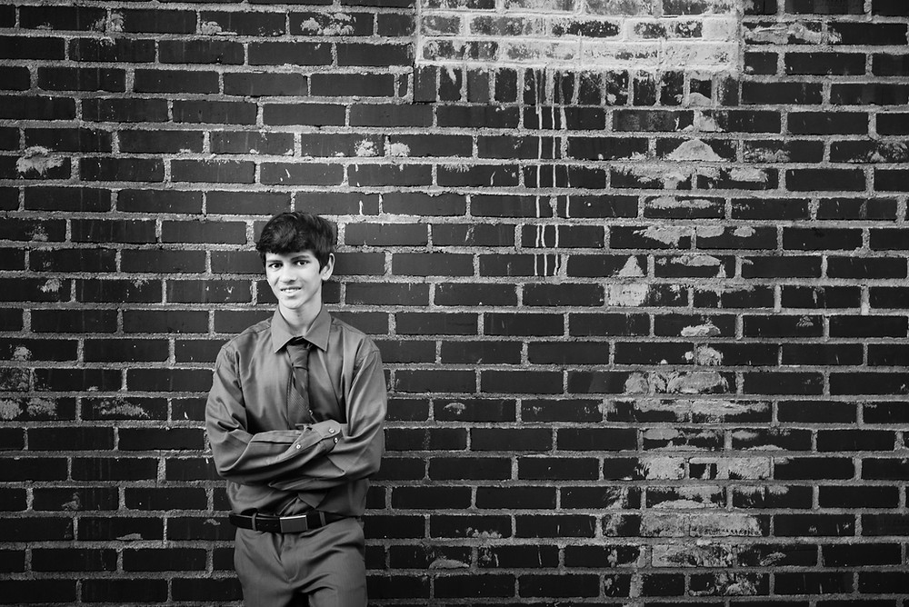 A black and white high school senior portrait in front of a brick wall.