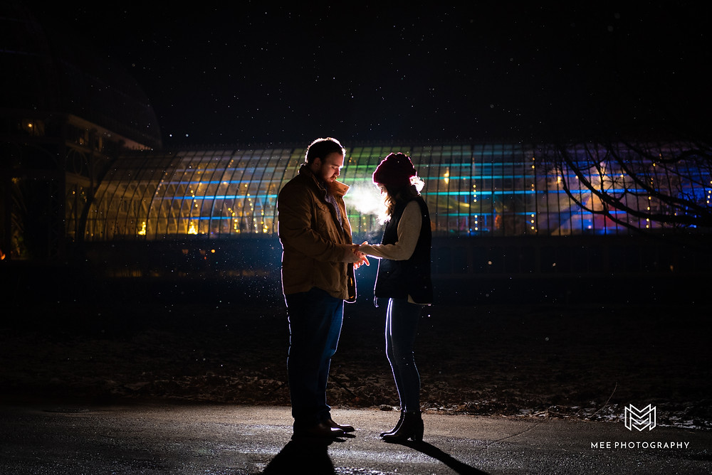 Christmas mini session in Pittsburgh at night with the couple holding hands and backlit by a flash