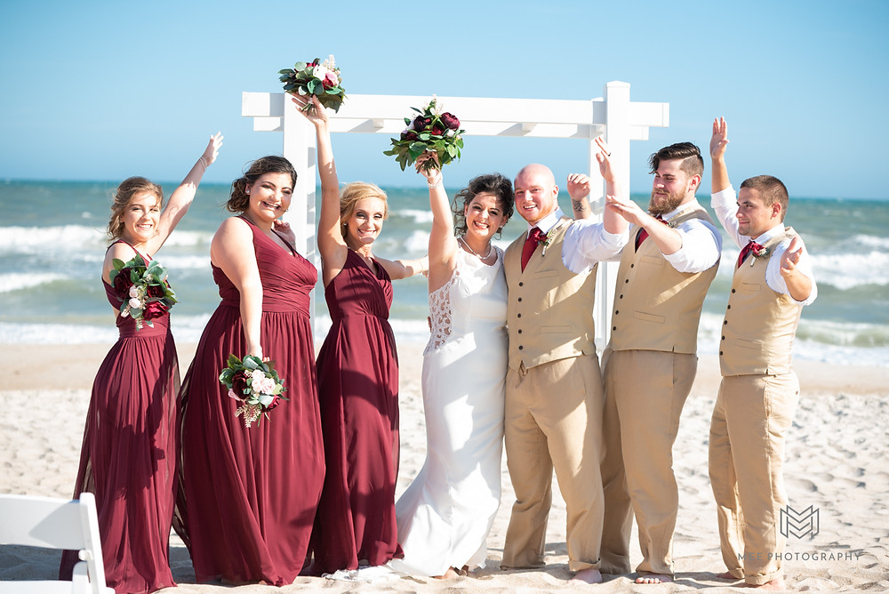 Bridal party celebrating after beach wedding