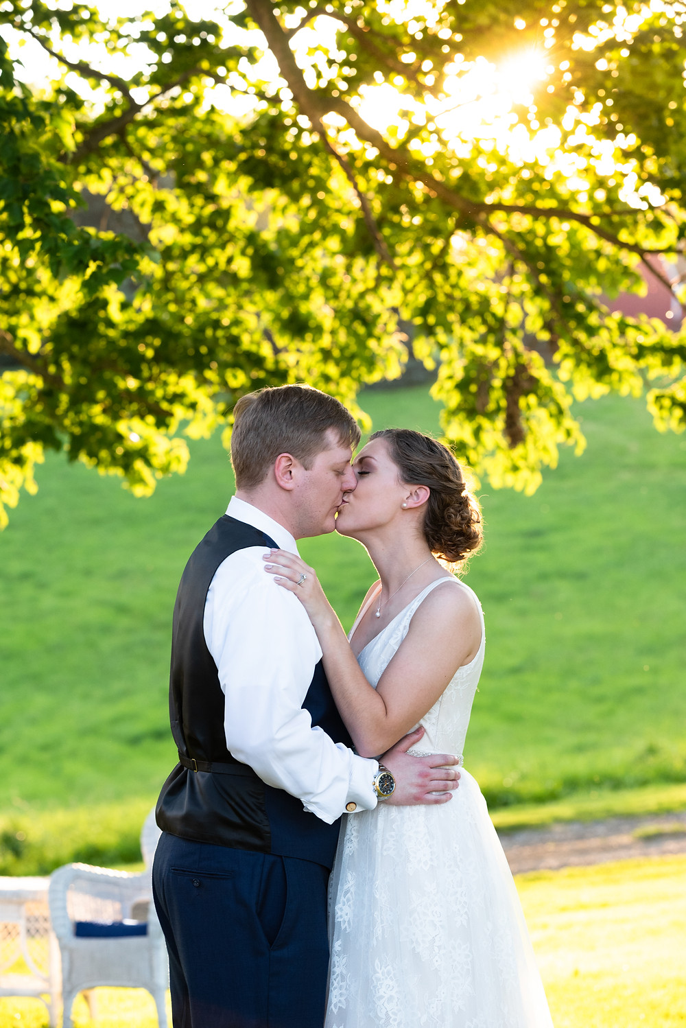 Bride and groom kissing in the golden hour sunlight at Lewis Family Farms