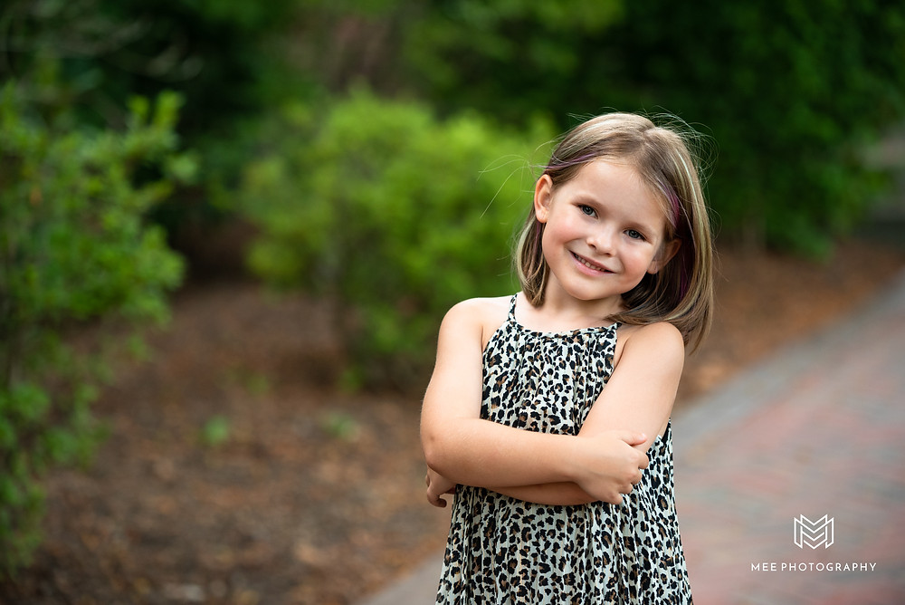 Five year old girl wearing a leopard print dress and posing for the camera at Bethany College