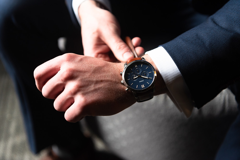 Wedding photographs of groom putting on his watch wearing a navy suit