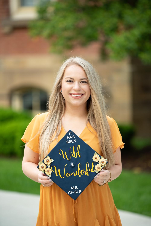 WVU graduation photos of girl holding her Wild and wonderful graduation cap