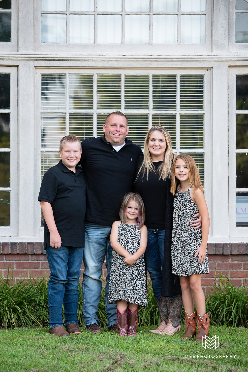 Family dressed in black and leopard print for their family session at Bethany College