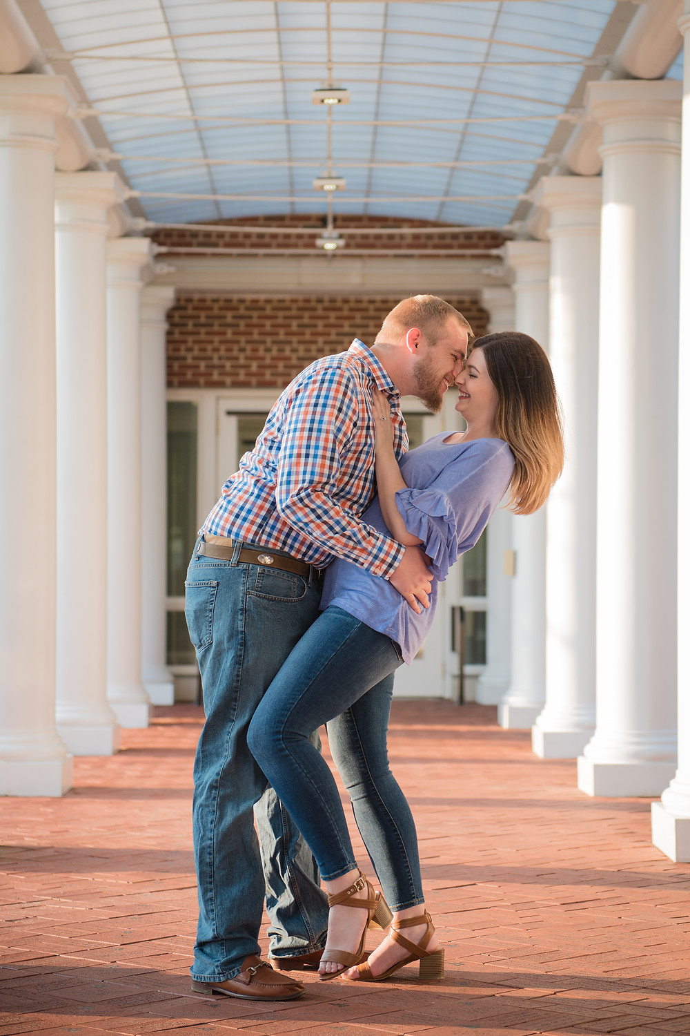 A West Virginia University engagement photo session. Picture taken in front of a campus building with white columns