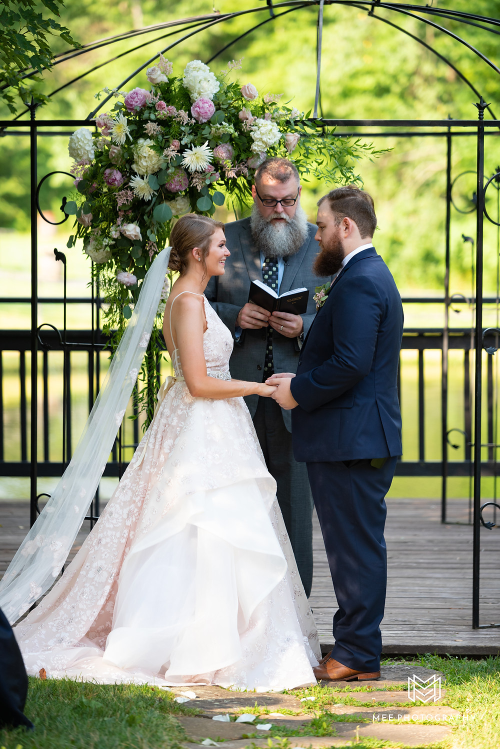 Bride and groom standing at the altar in front of a lake