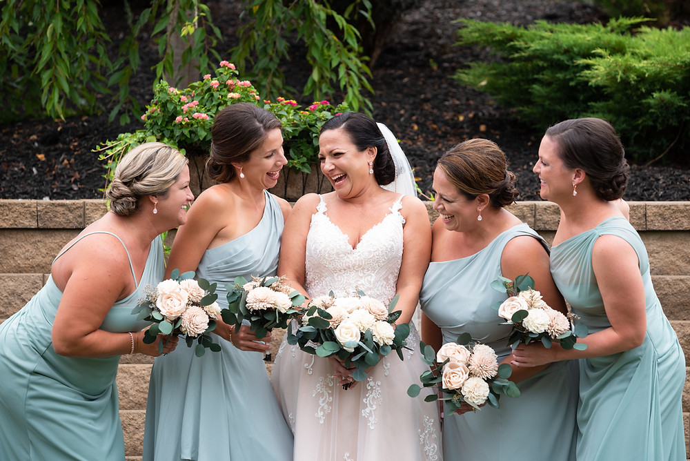 Bride laughing with bridesmaids in turquoise dresses