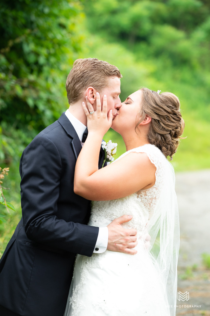 Bride and groom kissing as newlyweds