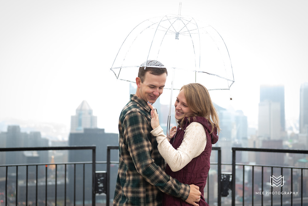Girl admiring her new diamond ring after her boyfriend proposed in Pittsburgh in the rain