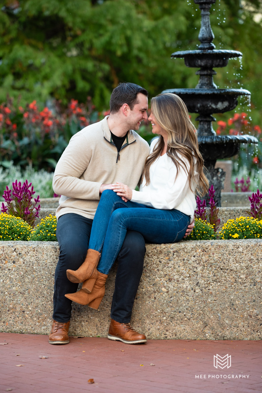 Couple sitting in front of Oglebay fountain during engagement photos