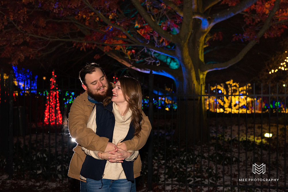 Couple laughing during their Christmas mini session at night in Pittsburgh
