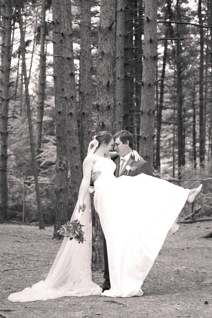 Groom picking up bride with pine trees in the background