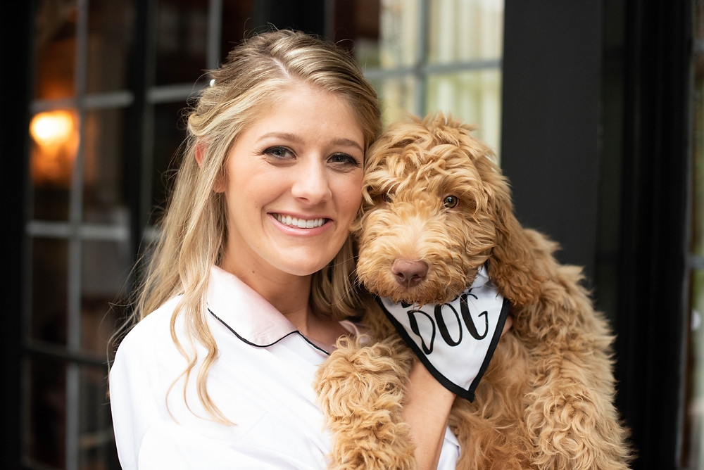 Bride posing with her golden doodle before the wedding
