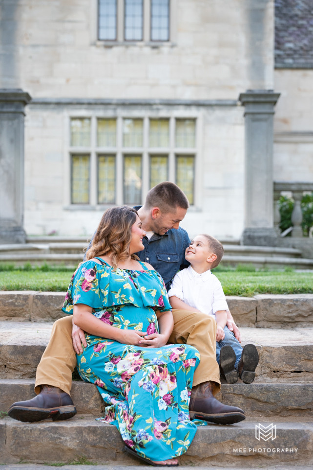 Family laughing on stairs during their family maternity session