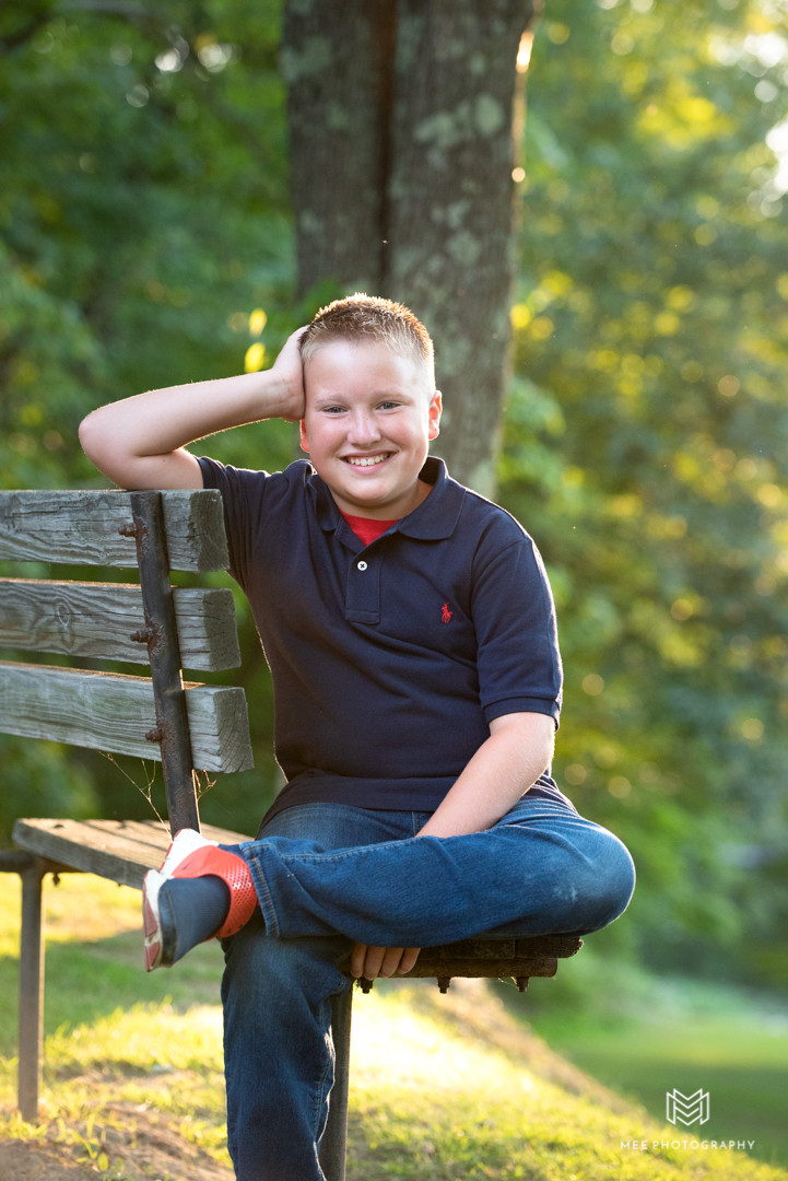 Portrait of a young boy sitting on a park bench in West Virginia