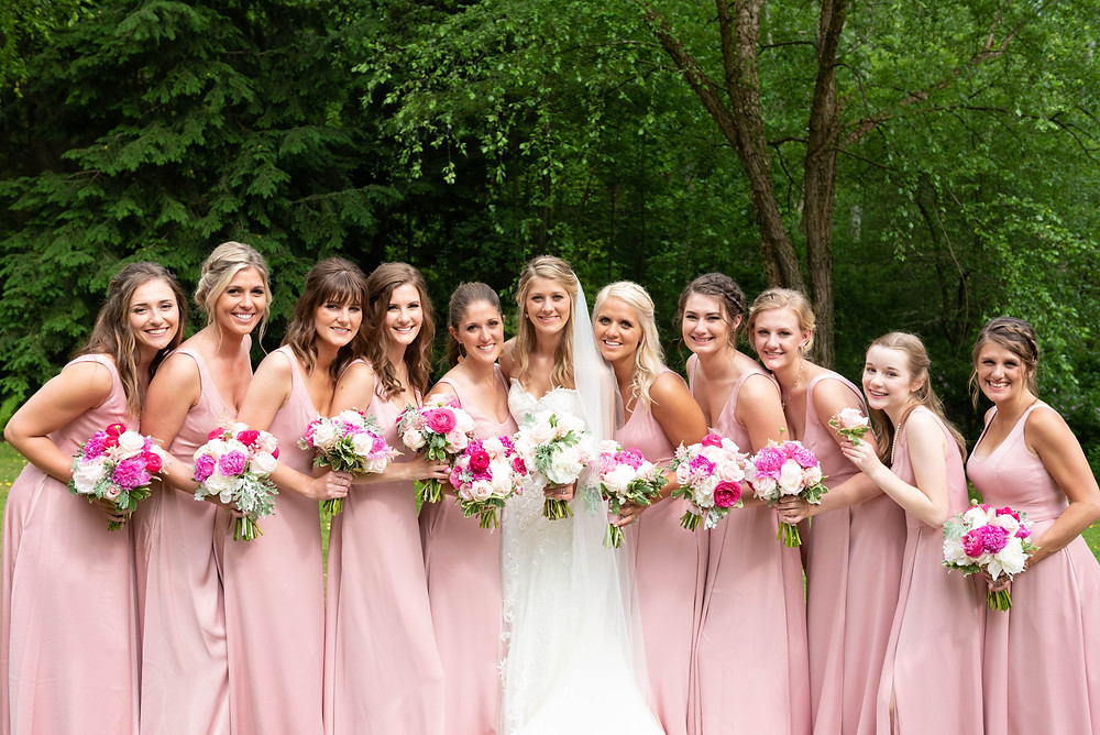 Bridal photograph with bridesmaids in light pink dresses; large bridal party posing ideas