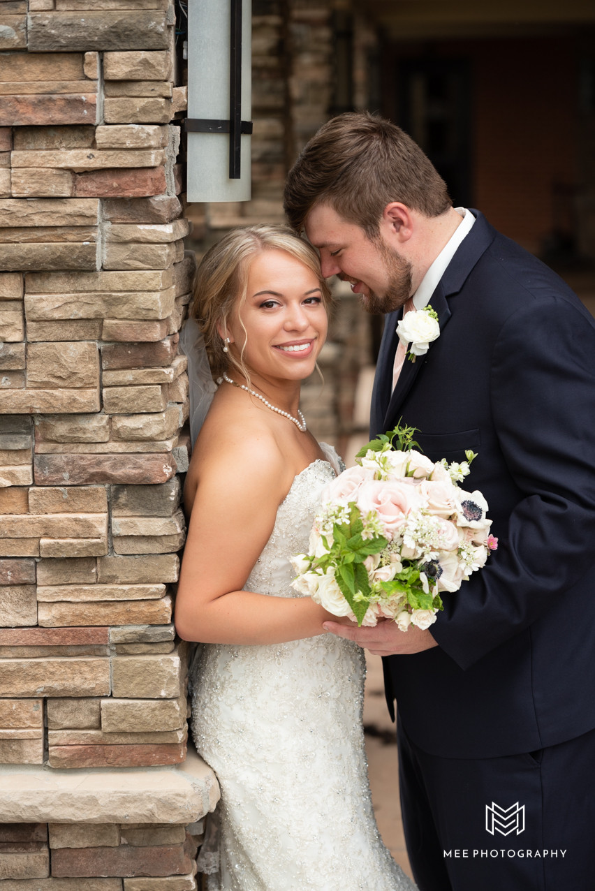 Bride and groom posed against stone wall at The Lake Club