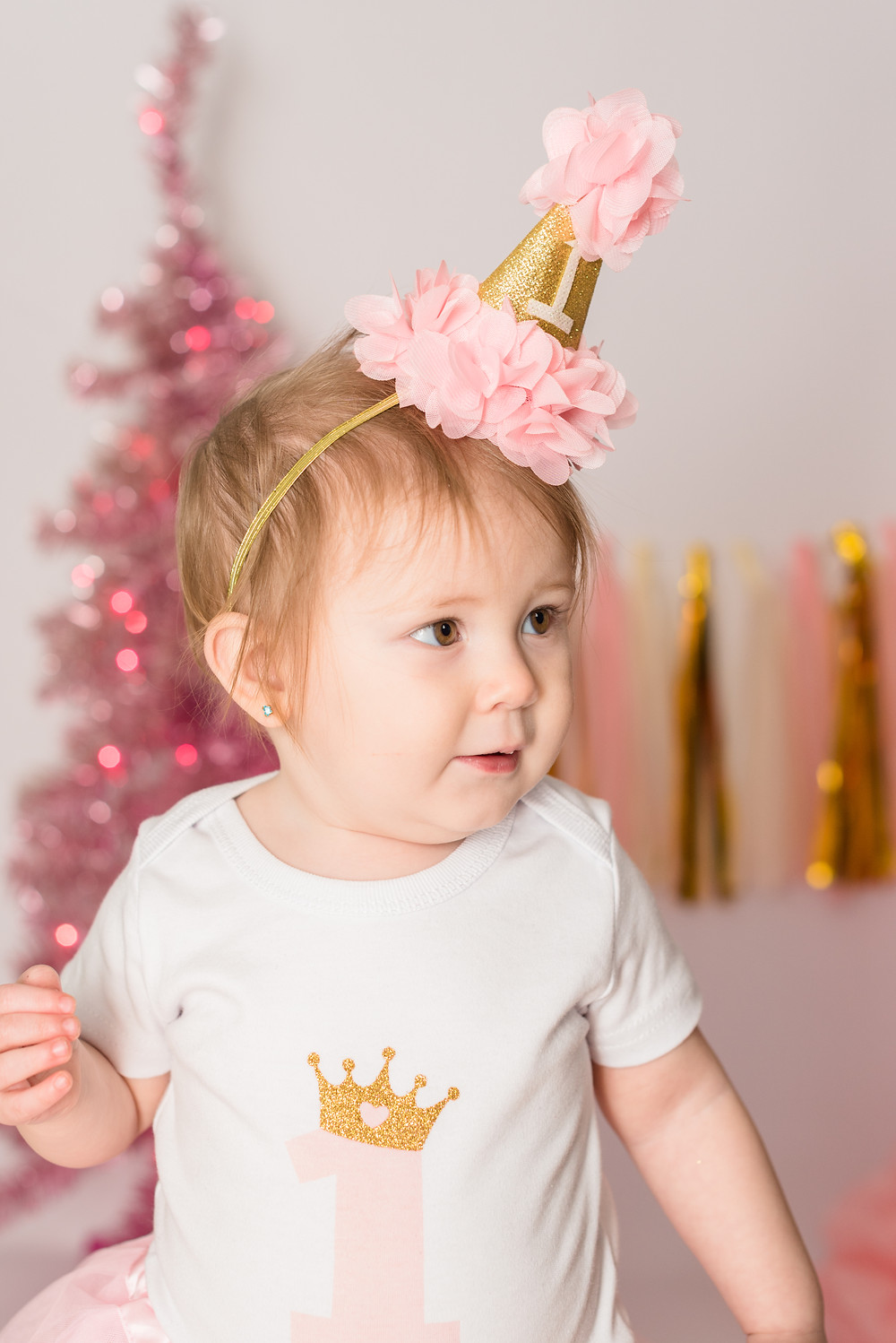 One year old girl celebrating her first birthday with a cake smash photography session. She is wearing a party hat.