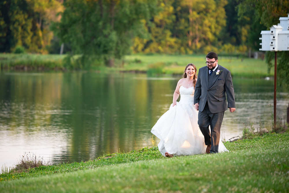 bride and groom walking along lake at Drake's Landing Banquet Center in Canfield, Ohio