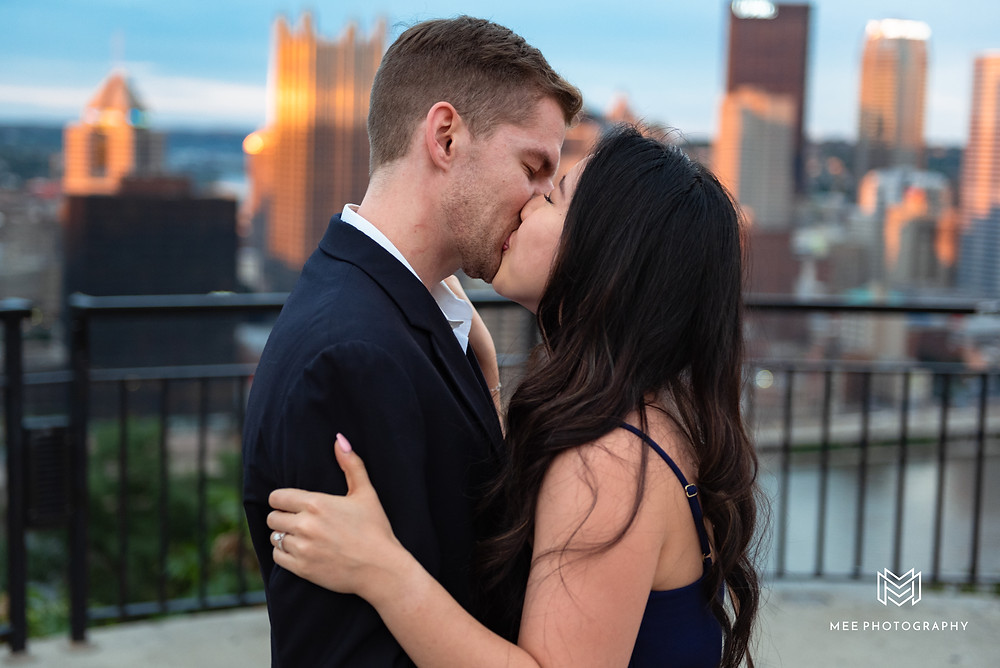 Couple kissing during proposal with Pittsburgh in the background
