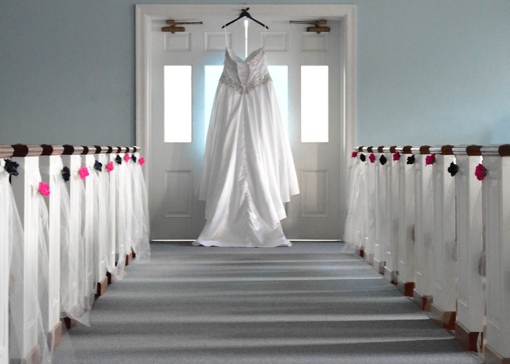 <alt>Wedding dress hanging in church before the ceremony</alt>