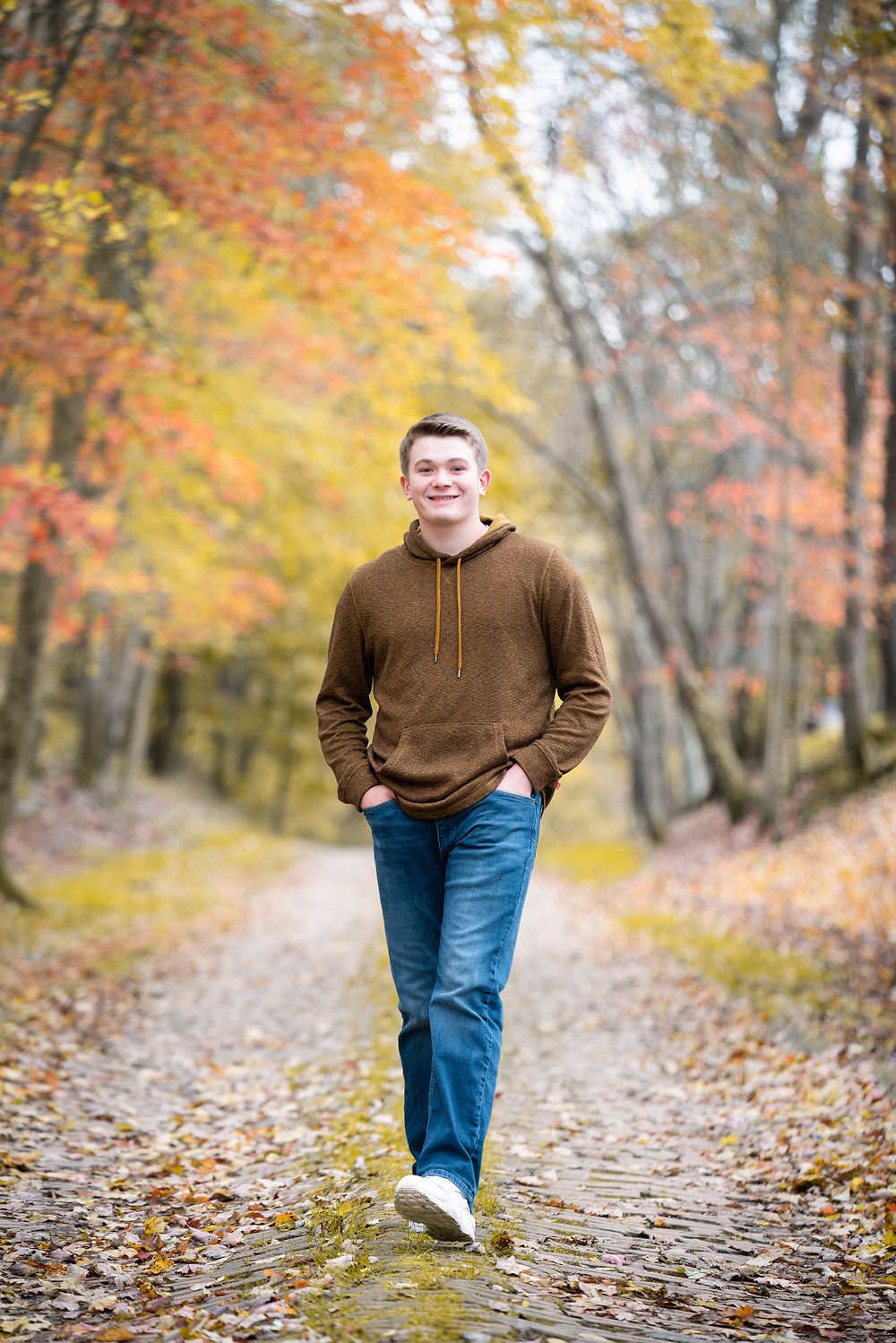 Senior guy walking down a brick path surrounded by fall leaves