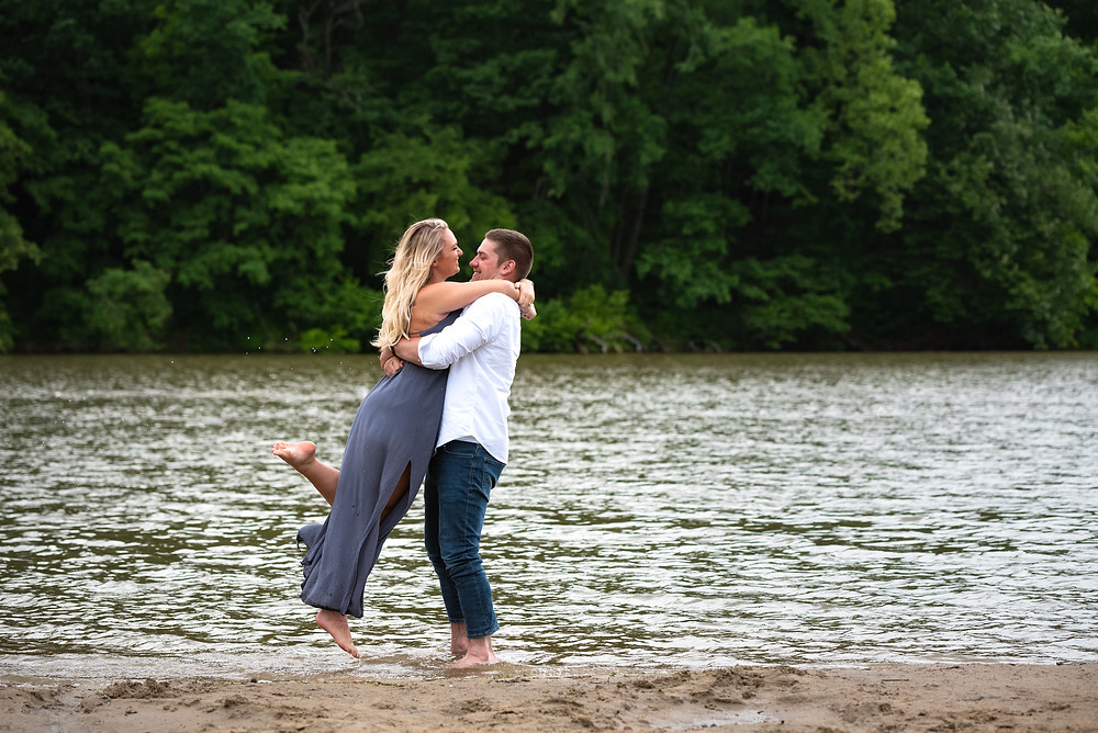 Guy lifting his fiance out of pond at Raccoon Creek State Park