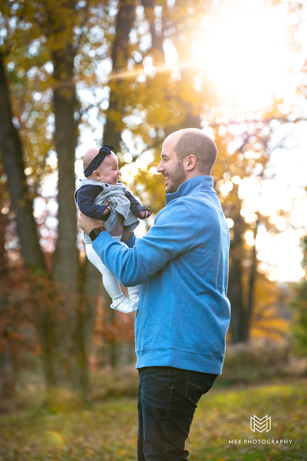 Dad holding baby in the fall sunlight at South Park, PA