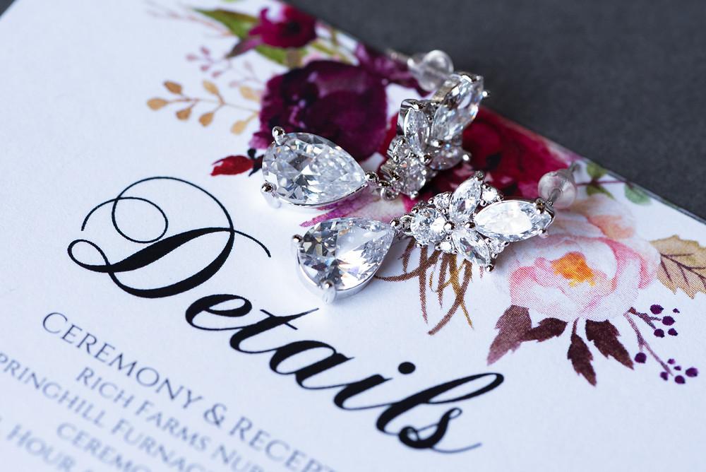 Diamond earrings on a details wedding invite card