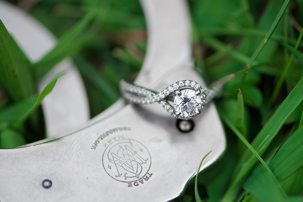 A silver engagement ring on handcuffs in the grass during this West Virginia engagement session.
