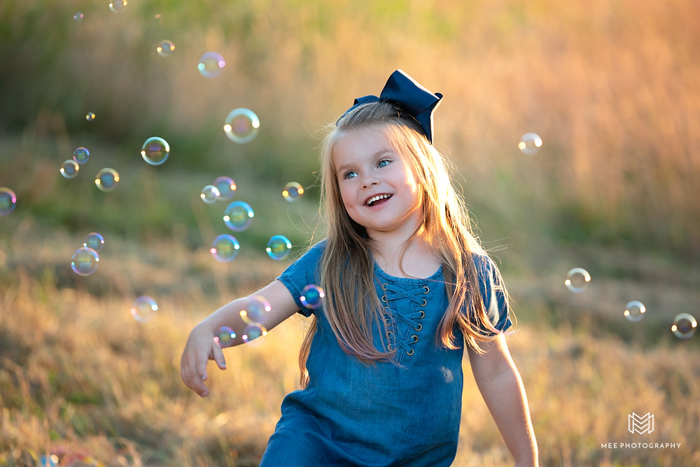Young girl playing with bubbles in a field at sunset