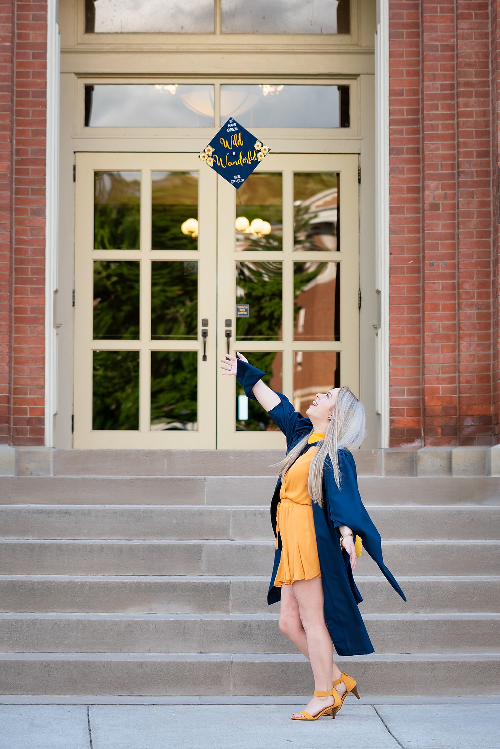 Girl throwing her blue graduation cap in the air at West VIrginia University