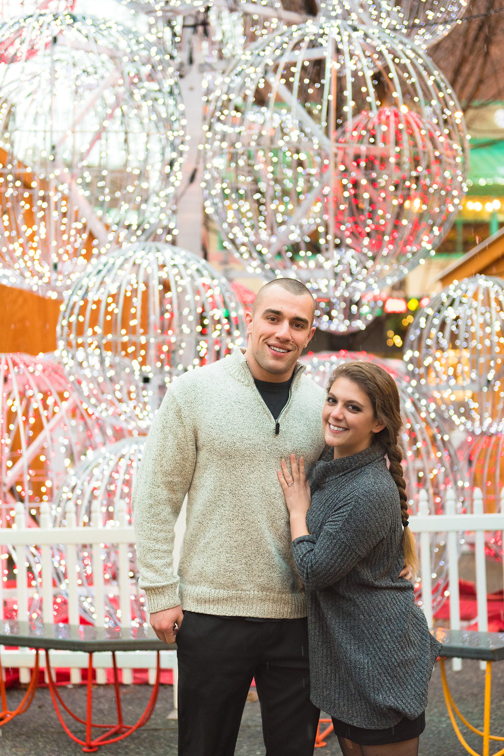 Couple posing for an engagement photo in front of christmas lights in Pittsburgh, Pennsylvania