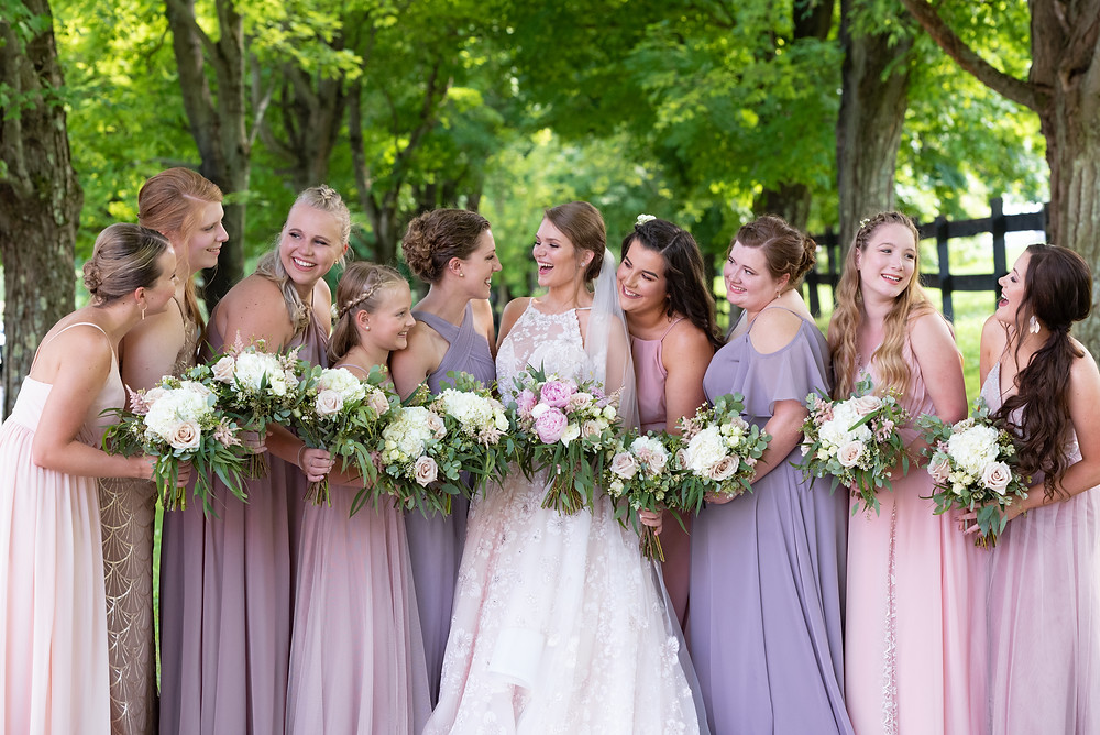 Bride and bridesmaids laughing in pink and purple dresses
